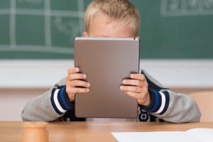 Boy obscured by tablet